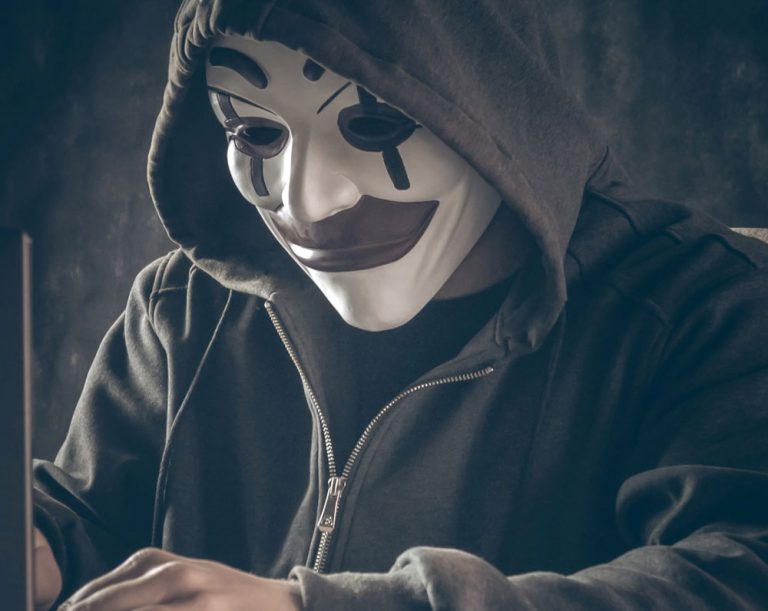 Man in clown mask at computer